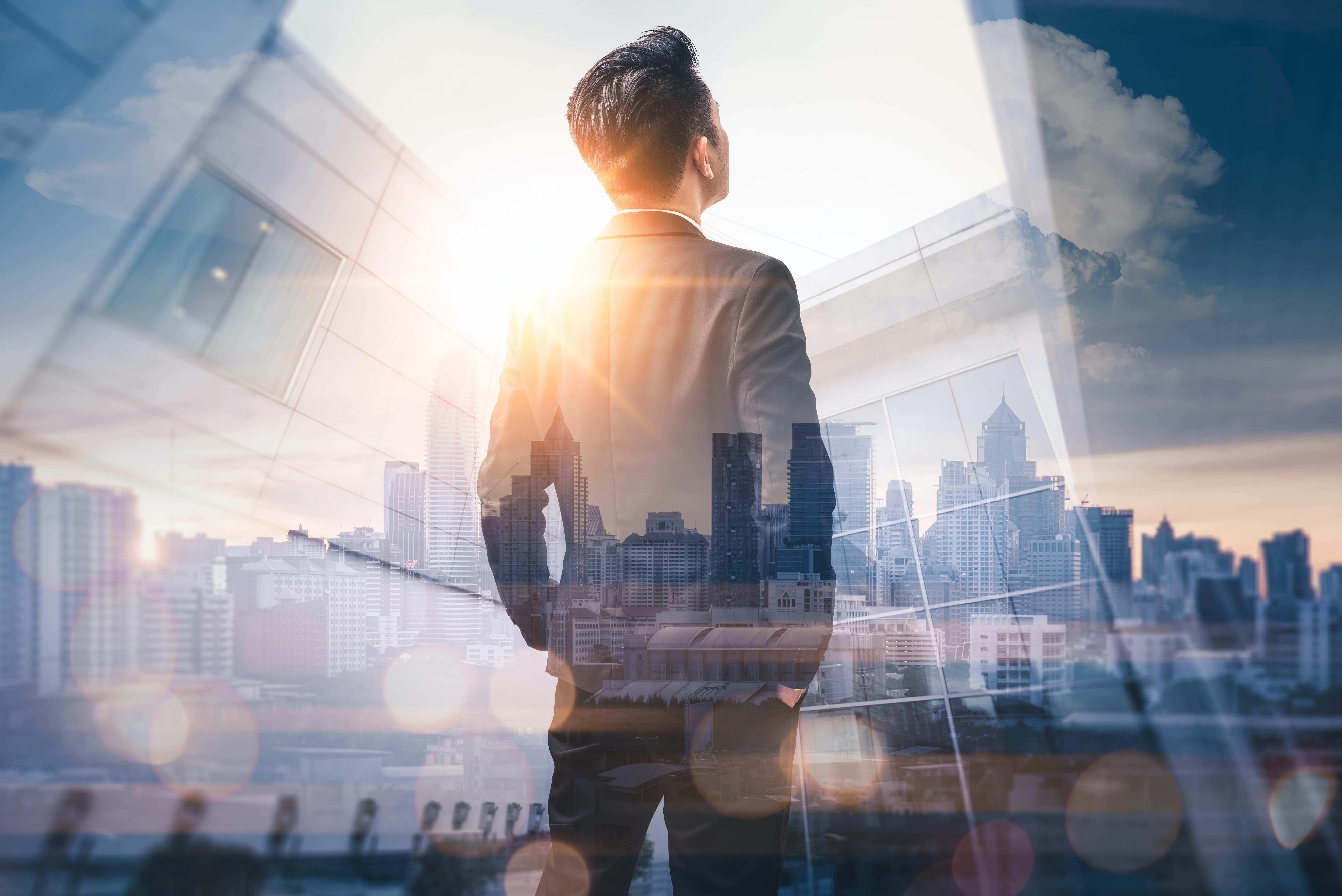 Business man standing back during sunrise overlay with cityscape